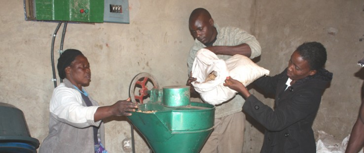 Vainess Phiri, right, and company load peanuts into the expeller.