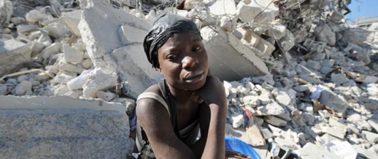 A Haitian woman rests on the rubble of a destroyed building at a market in Port-au-Prince following a massive 7.0-magnitude quak