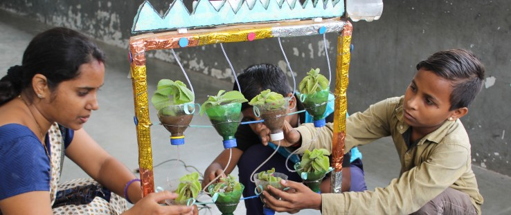 A teacher helps students perform a science experiment at Kavi Kalidas Primary School.