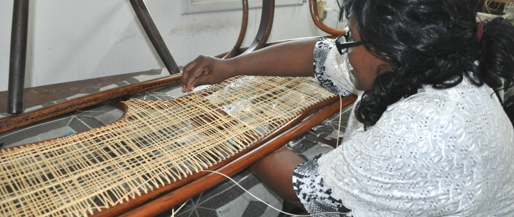 Claudette Thompson demonstrates her skills by caning one of many chairs for her organization Superior Crafts and More Ltd.