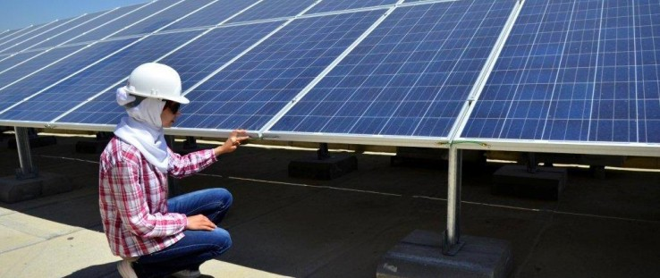 Ala Al Shareef installs solar panels on the roof of Jordan's Ministry of Planning and International Cooperation.