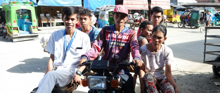 A nurse from the Maragusan Rural Health Unit, left, gets ready to visit patients in surrounding villages on a motorcycle taxi.