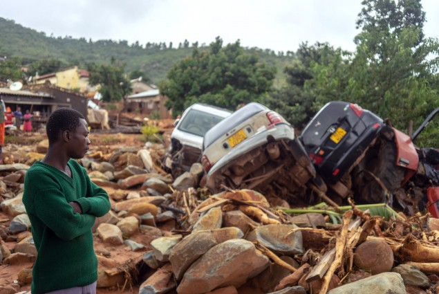 A man stands next to the wreckage a vehicles washed away on  March 18, 2019 in Chimanimani, eastern Zimbabwe, after the area was hit by the cyclone Idai. - A cyclone that ripped across Mozambique and Zimbabwe has killed at least 162 people with scores more missing. Cyclone Idai tore into the centre of Mozambique on the night of March 14 before barreling on to neighbouring Zimbabwe, bringing flash floods and ferocious winds, and washing away roads and houses. (Photo by Zinyange AUNTONY / AFP)