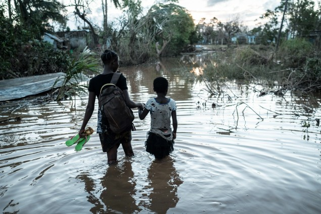 Rosita Moises Zacarias (L), 15, holding the hand of her sister Joaninha Manuel, 9, walks in flooded waters from their house destroyed by the cyclone Idai, to go to seep in a shelter in Buzi, Mozambique, on March 22,