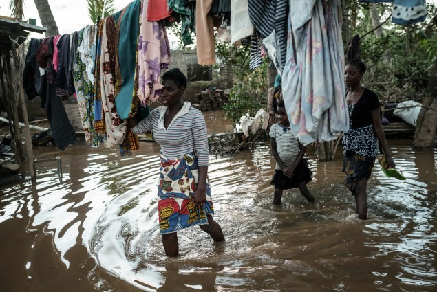 Albertina Francisco (L), and her daughters Rosita Moises Zacarias (R), 15, and Joaninha Manuel, 9, walk in flooded waters from their house destroyed by the cyclone Idai as they go to seep in a shelter in Buzi, Mozambique, on March 22, 2019.