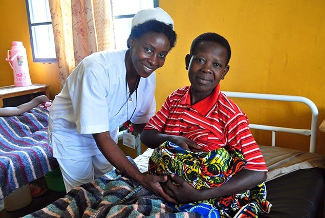 A nurse helps a new mother at a hospital in Rwanda