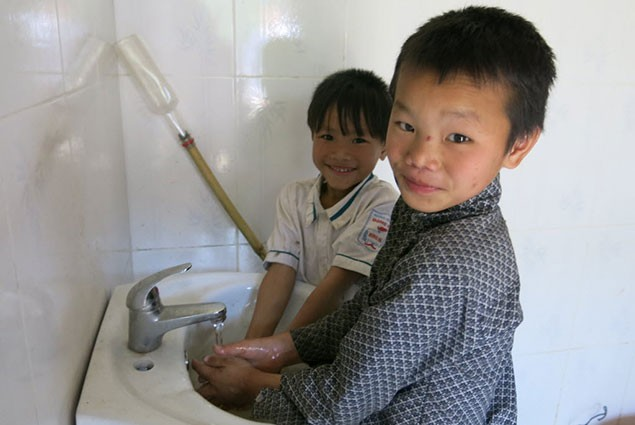 Two boys was their hands in a bathroom sink
