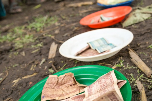 Collection plates for Nigat Chora (Sunrise) Village Economic and Social Association (VESA). Each plate bears money for a different function--regular savings,  social fund, penalties and late payments. Comprised of groups  of neighbors and peers, VESAs are the foundation of all USAID-supported activities. VESAs also provide savings and credit facilities to members. When Nigat Chora was established five years ago, its 23 member households were some of the poorest in the community. Today a 'culture of saving'