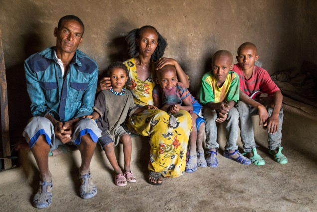 As a model farmer and VESA (village economic and social association) chairperson, Etsay Wayu (left) helps his fellow VESA members gain the knowledge, skills, and confidence they need to turn their lives around. Here Etsay is pictured at home with his family. Thanks to USAID, he and his wife, Mulu Girmay, have learned new ways to manage their farm and their income. As a result, they have more than a year's worth of food in storage.