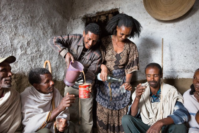 Berhe Desta and his wife Zenebu Shomoy serve customers at their tella bet (an informal bar that sells local alcohol). Berhe and his wife Zenebu work together in oxen fattening. They used some of the profit from their business to construct a new house for their family. Then they decided to generate additional income by using the front room of that house as a tella bet.