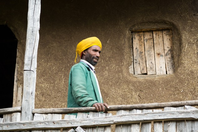 Getachew Tadesse on the porch of his new house. Like many USAID beneficiaries, Misaye Akele (not pictured) and her husband Getachew Tadesse (pictured) feel that the greatest changes to their lives and livelihood have come about as a result of the USAID's training on gender. By stepping out of traditional gender roles and working together, they are not only happier, but also better off. This year they put much of their extra income into building the family a new house.