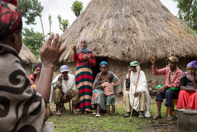 A member of Nigat Chora (Sunrise) Village Economic and Social Association (VESA) raises her hand to speak and is called on by Community Facilitator Zemsem Kefir during a VESA meeting. Comprised of groups  of neighbors and peers, VESAs are the foundation of all USAID-supported activities. VESAs also provide savings and credit facilities to members. When Nigat Chora was established five years ago, its 23 member households were some of the poorest in the community. Today a 'culture of saving' has helped transf