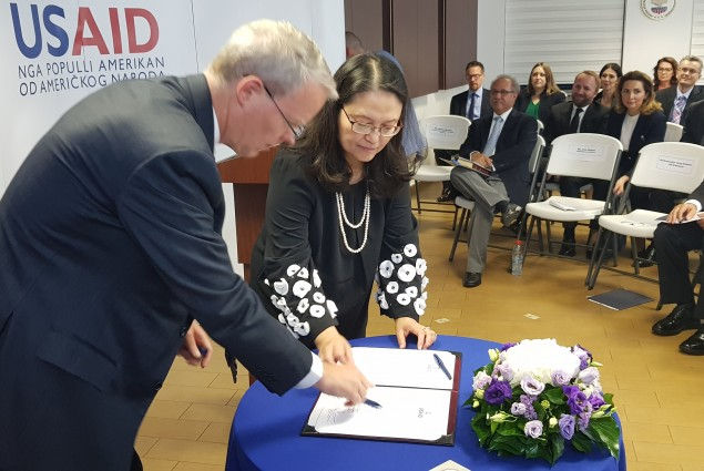 Ambassador Delawie and Lisa Magno sign the Oath of Office