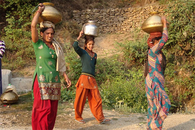 Three women carry jugs of water on their heads