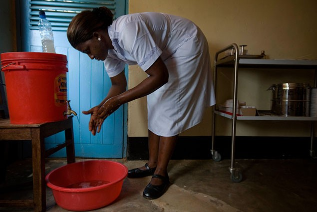 A woman washes her hands with water from a bucket with a spigot