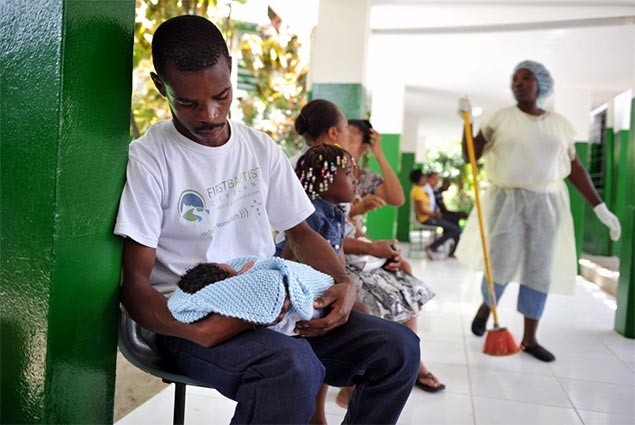 A father looks down at this newborn child in Haiti