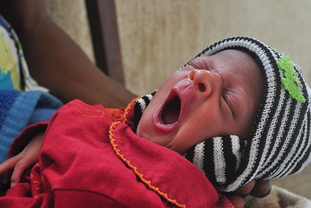 A newborn baby yawns while being held