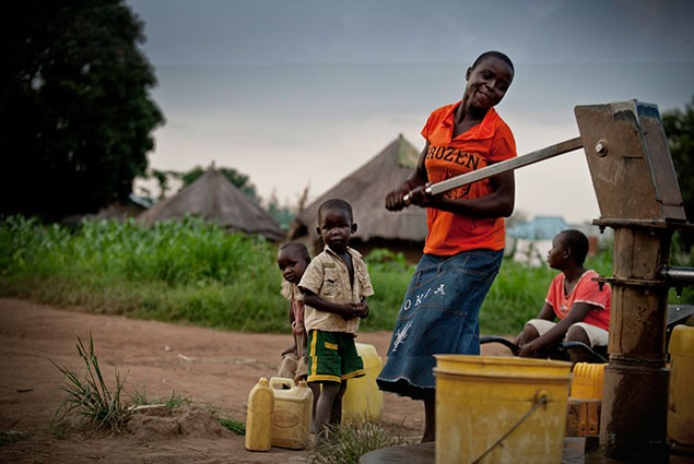 A woman pumps water into a bucket while children wait behind her to fill their containers