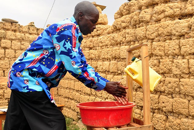 A man washes his hands from a make-shift water source.