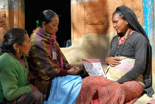 A new mother sits with others from her village