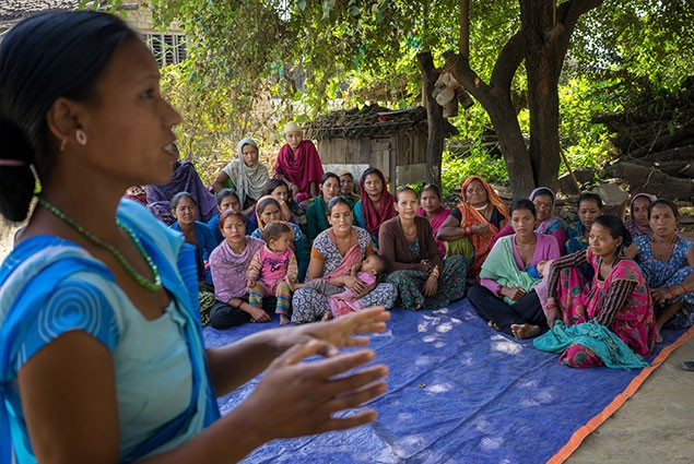 A health worker talks to a group of women.