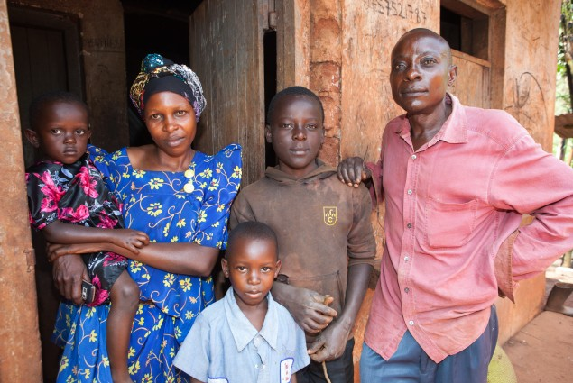 A husband, wife, and their three children stand in front of their home.