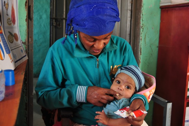 Natsaannat, a health extension worker in Wara Village, Ethiopia, counsels Aynamam on how to treat malnutrition in her child, Bitu.