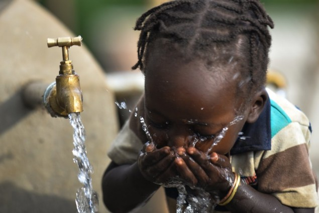 Image of girl in Ethiopia drinking from water tank