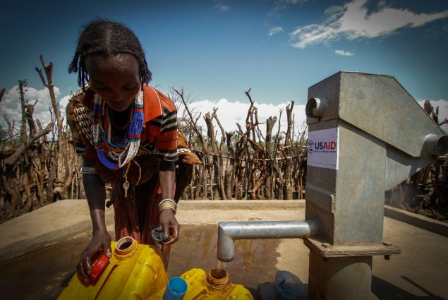 Image of woman in Ethiopia pumping water in village of Buluko