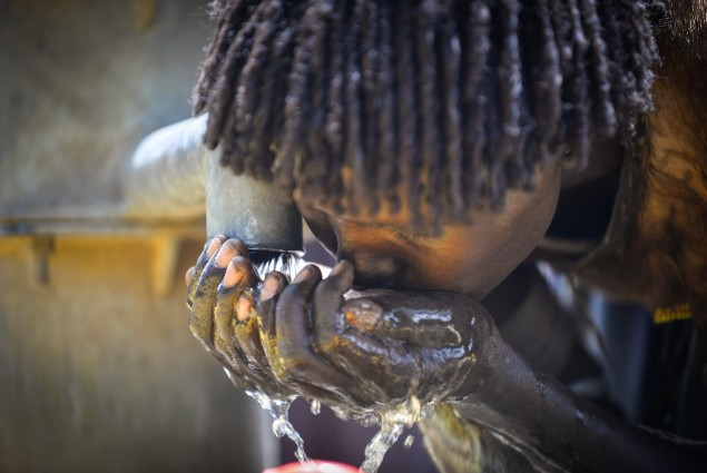Image of woman drinking water from pump in Ethiopia