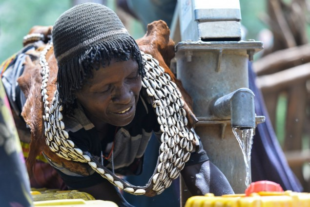 Image of woman in Ethiopia filling water jugs