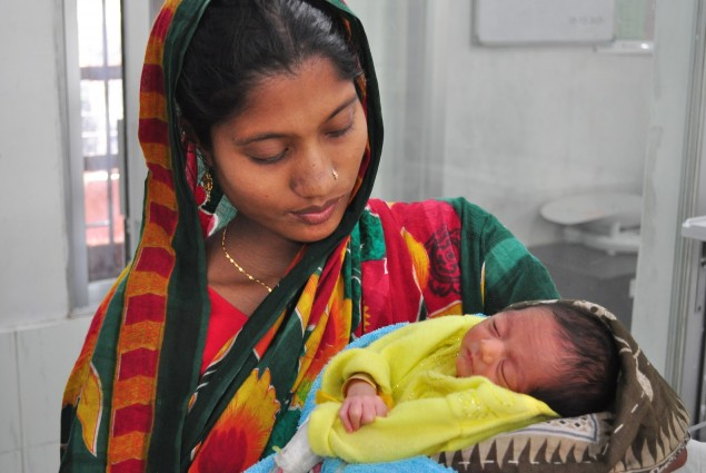 A health worker holds a newborn child