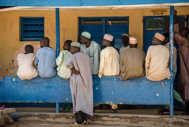 A group of men in Nigeria waiting for their wives outside a health clinic in Nigeria