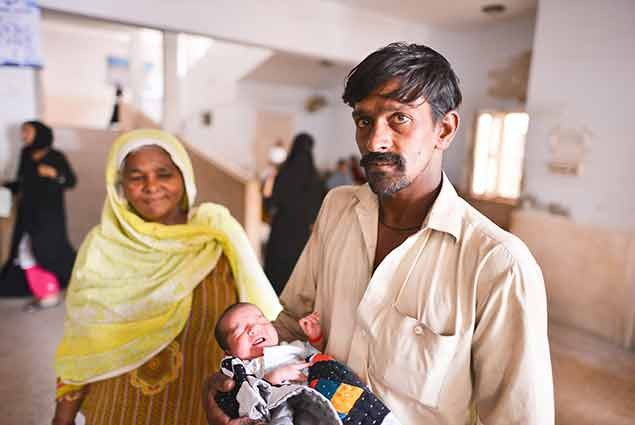 A father holds his new born child in Pakistan