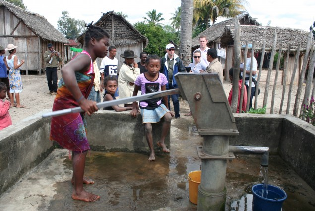 Girl pumping out water from the village's only water supply point