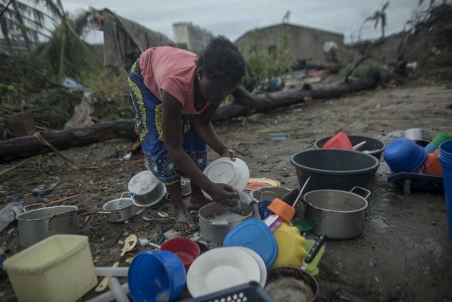 "Mariamo Humberto, washes dishes at her family's home that had all but been destroyed. ""When the storm started we began running to find a safe place. We had no food and our clothes were soaked We couldn't believe to be alive. We were very scared when the storm started. And now we are here. We have lost clothes and even food. Everything is wet including clothes."" Photo by  Josh Estey/CARE"