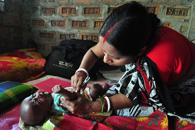 A community health worker examines a newborn baby.