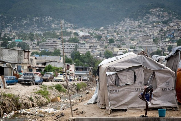 A Haitian man washes outside of an emergency shelter in Port-au-Prince, Haiti