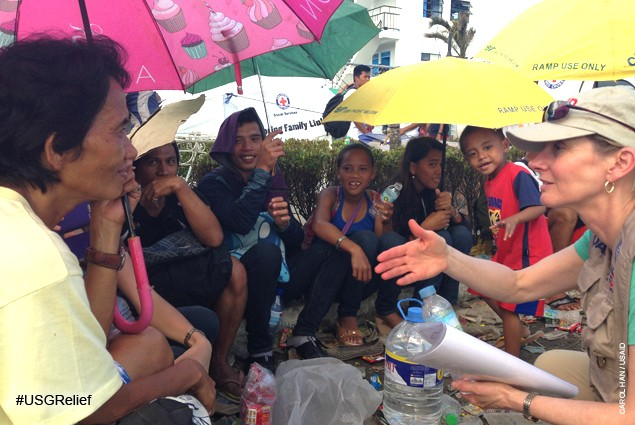 USAID Assistant Administrator Nancy Lindborg with evacuees outside Tacloban airport. Evacuees are flown to Manila aboard militar