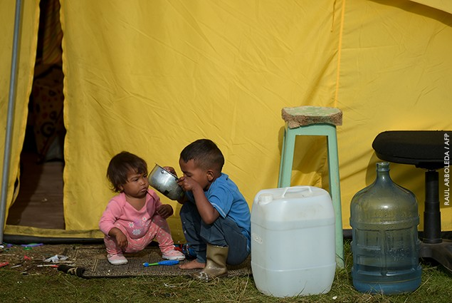 Venezuelan migrant children are seen outside a tent in a humanitarian camp in Bogota on January 9, 2019.