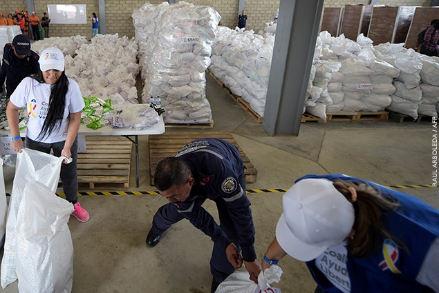 Volunteers and firefighters arrange bags with US humanitarian aid goods in Cucuta, Colombia, on the border with Tachira, Venezuela.