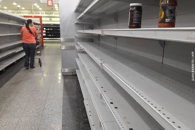 A woman walks between the empty shelves of a supermarket in Caracas, Venezuela.