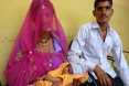 A father and mother with their newborn child in India
