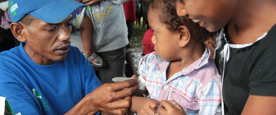 A health worker in Timor-Leste monitors the growth of a child.