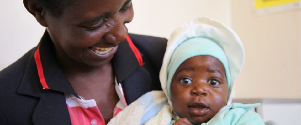 Rosemary proudly holds her HIV-free baby after receiving prenatal treatment from a USAID-sponsored clinic outside Harare, Zimbab
