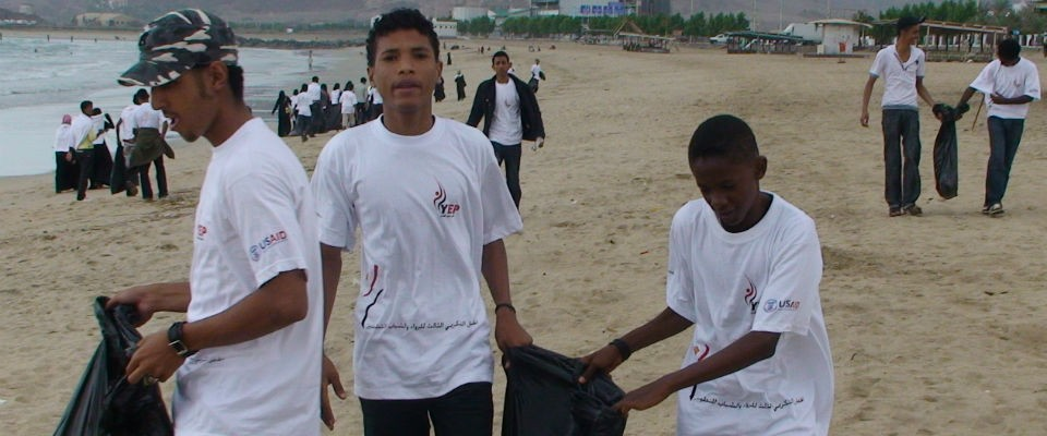 Young volunteers clean up a beach in Aden as part of USAID-supported activities for International Volunteer Day.