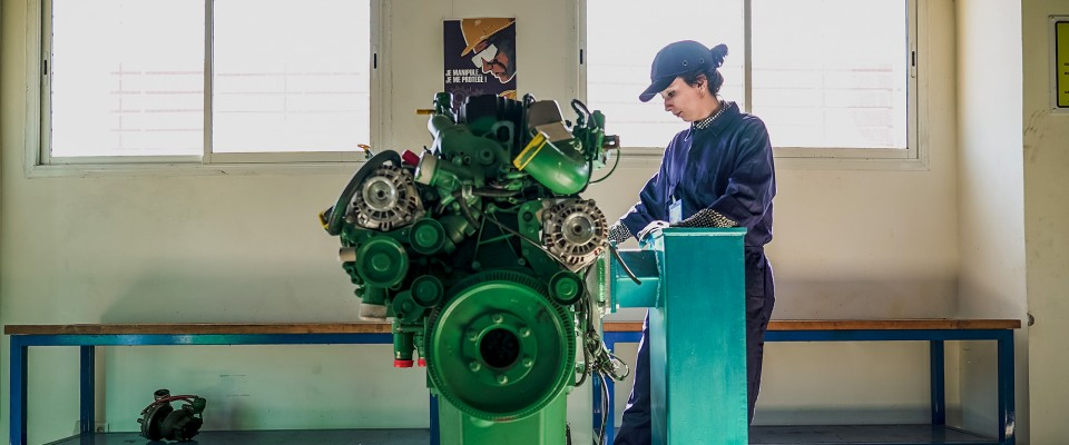 Maria works on a Volvo engine at the USAID-funded vocational training center