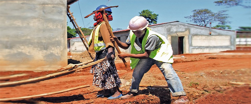 Female and male workers on the construction site of a health facility