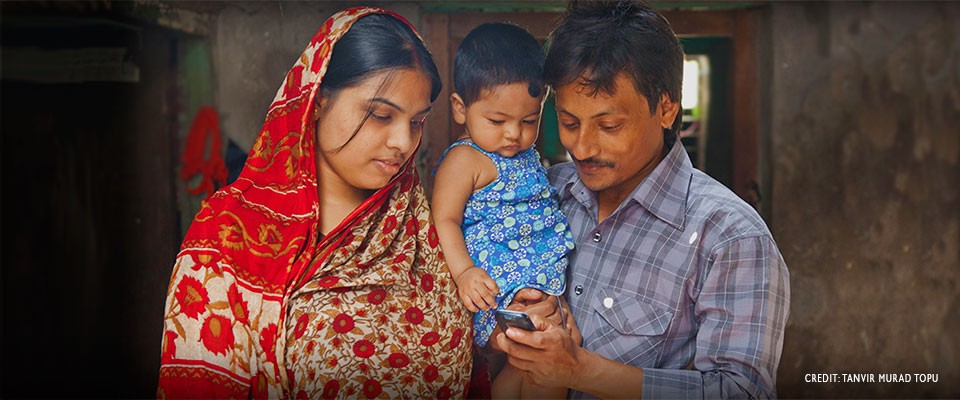 Image of Bangladesh family using mobile phone for health information.