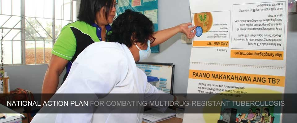 Health provider examines an educational flipchart about tuberculosis in Ibaan, Philippines